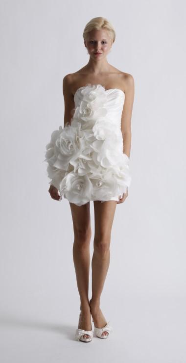 MARCHESA Robe de mariée baby doll drapée et agrémentée de fleurs qui apportent du volume sur toute la longueur de la robe.  Photo : Marchesa ©
