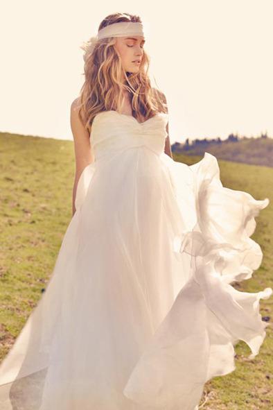 REMBO STYLING Robe de mariée coupe Empire. Grâce au matières très fluides, le mouvement de la robe masquera les rondeurs.  Photo : Rembo styling ©