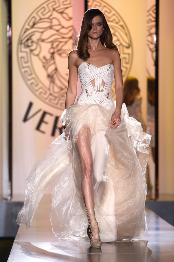 VERSACE A elle toute seule, la griffe Versace est le symbole de la féminité. A la fois sexy et élégante, cette robe de mariée pin-up est une invitation évidente au glamour et à la volupté. Un bustier lacé et ajouré à tendance vinyle, un jupon en tulle fluide et brillant pour de divines gambettes: il faut oser!  Crédit photo : VERSACE