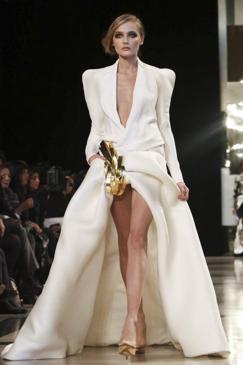 GEORGES HOBEIKA Un tissu simpliste doublé d\'une forme audacieuse, voilà l\'équation parfaite de cette robe de mariée griffée Georges Hobeika. Un haut doté d\'épaulettes masculines façon complet et un jupon raccourci de manière un peu... osée, voilà un ying et yang juste parfait!  Crédit photo :GEORGES HOBEIKA