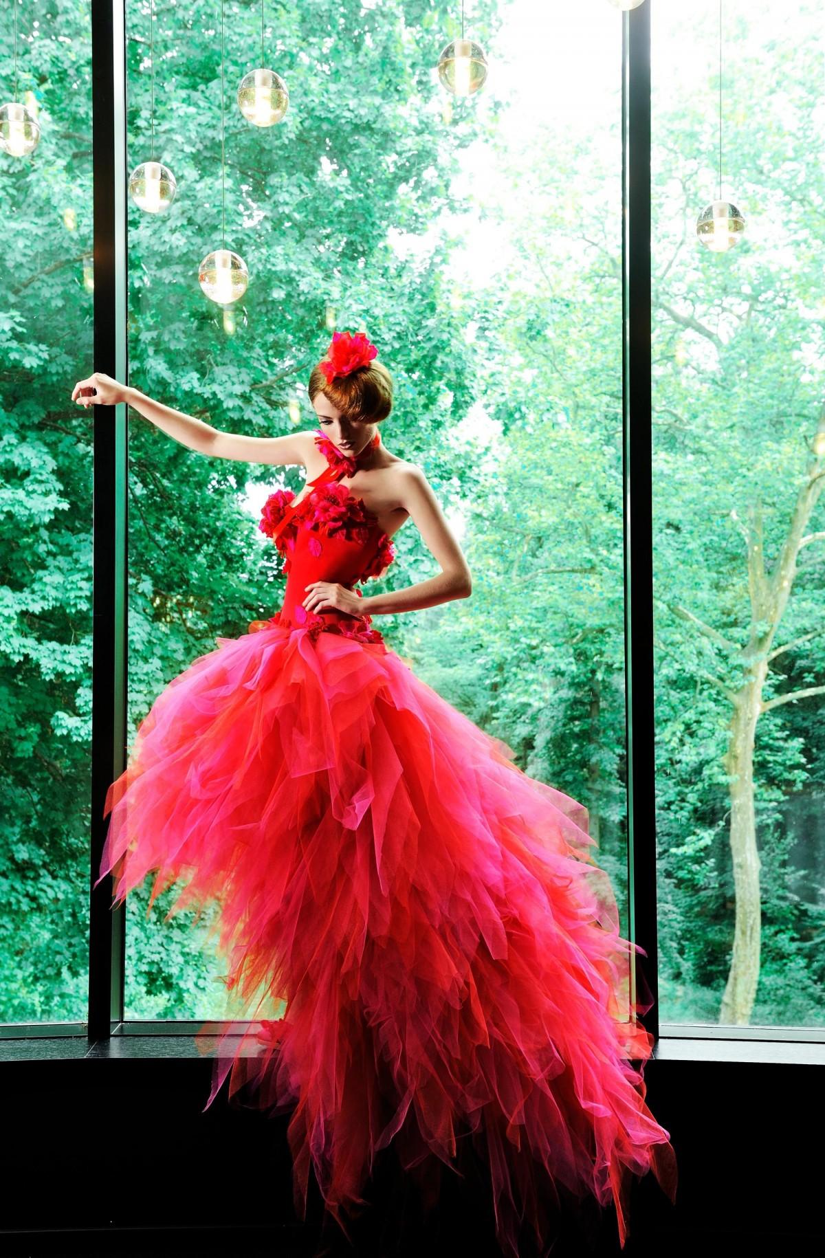 Rouge, fuschia et matières nobles pour cette robe signée Nicolas Fafiotte: un bustier de satin duchesse, des fleurs de soie et une jupe en foulards de tulles, cette robe de mariée éclatante est lacée dans le dos.