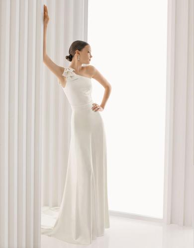 Le modèle Armenia est une combinaison-pantalon de mariée au décolleté asymétrique orné d'un ruban de crêpe: un modèle épuré et très élégant en satin de soie. Prix sur demande.       Photo DR