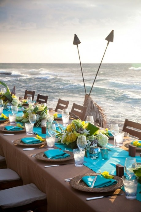 Manger les pieds dans le sable pourrait être un des moments forts de votre futur mariage à la plage. Pour poser la vaisselle, on opte pour cette nappe couleur taupe qui permet d'éclairer la table avec des détails jaune citron. Très réussi!