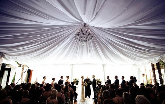 Un immense drapé blanc attaché par un lustre éclatant, votre plafond habillé ainsi illuminera votre cérémonie. Vos invités ne pourront pas résister à regarder en l'air jusqu'à votre arrivée dans votre robe de princesse !