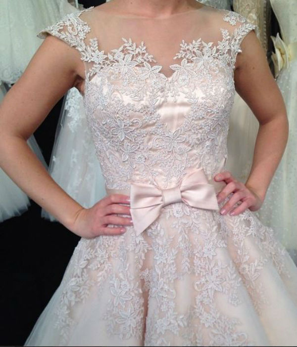 """Chez Royal Lace Bridal, on aime l'idée d'agrémenter notre robe de mariée par une ceinture pour marquer la taille. Ici, c'est un joli noeud rose, mais cela pourrait être une ceinture plus """"classique""""."""