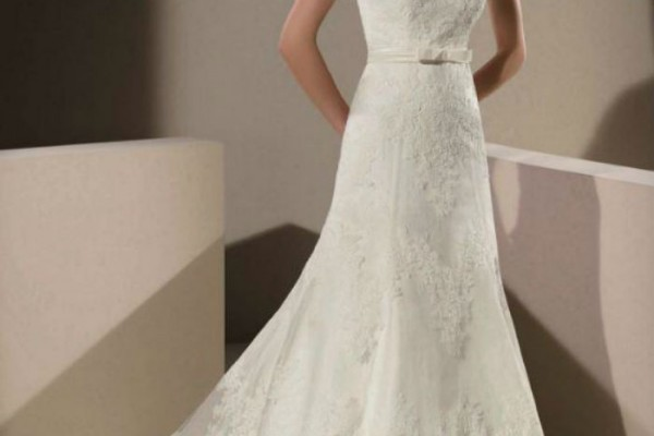 Sur cette robe de Divina Sposa, la dentelle est aussi très présente. Transparente sur le haut du bustier en forme de coeur, elle est parsemée par petites touches sur le jupon. Une ceinture vient joliment resserrer la taille.
