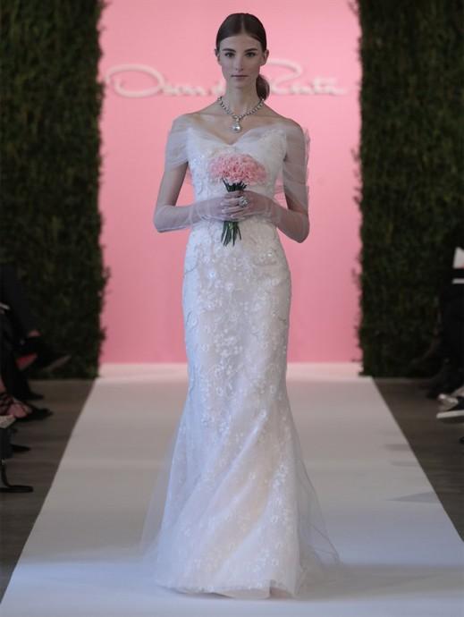 Cette robe d'Oscar de la Renta est romantique à souhait : un léger voile recouvre les bras jusqu'aux épaules. Plutôt près du corps, de beaux points de dentelle parsèment la robe. Ici pas de demi mesure, les manches viennent couvrir jusqu'au bout des doigts !