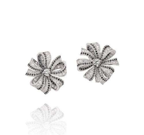 Si vous souhaitez des boucles d'oreilles chic mais discrètes, pourquoi ne pas choisir cette paire dont les petits rubans forment une fleur ? Elles sont magnifiques ! Boucles d'oreilles 1932 de Chanel, en or blanc 18 carats, diamants noirs et diamants, prix non communiqué.
