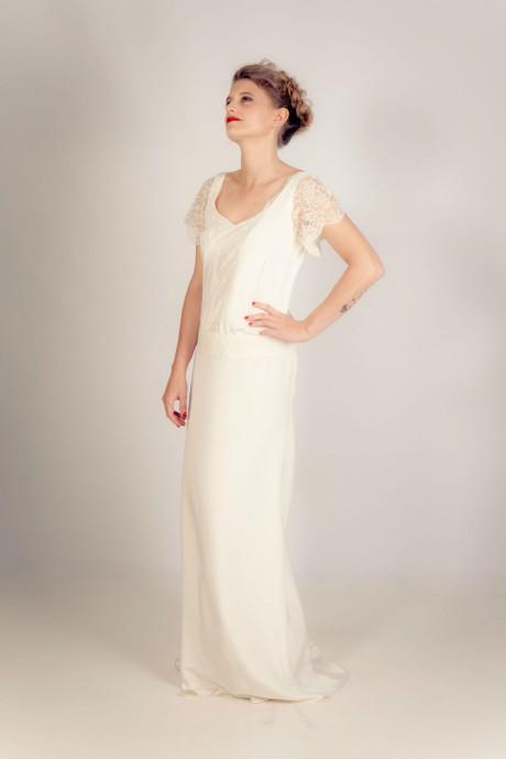 Cette tenue de Stéphanie Wolff, relativement discrète est parfaite pour les futures mariées voulant être sobres. Les petites bandes de dentelles sur les épaules ainsi que sur le devant de la robe offrent un aspect romantique à l'ensemble. Le vernis et le rouge à lèvres rouge apporte la touche de glamour et de chic attendu pour une mariée dans le style vintage.