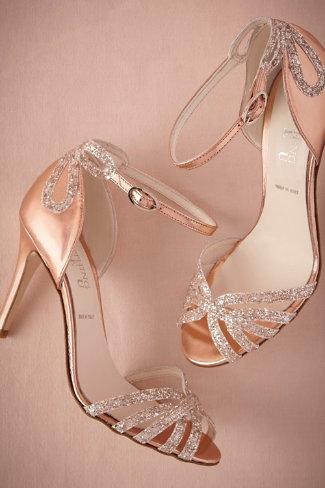 Pour terminer cette sélection de chaussures de mariées brillantes, on craque pour ces sandales de ce créateur de robes de mariées que l'on aime beaucoup. Le tissu est métallisé, d'une teinte rose doré. Les talons sont de 9 cm environ, mais la chaussure assure un bon maintien avec ses nombreuses brides. L'une d'elles, à la cheville, est ajustable. Par-dessus est cousu un joli nœud en strass. On retrouve ces brillants sur les brides croisées au bout du pied. De vraies chaussures de princesse, qui font aussi « danseuse étoile », vous ne trouvez pas ? Les petits rats de l'opéra dansent à plat, certes, mais la couleur de leurs chaussons nous rappellent ces souliers de mariée. Enfin, ils ont été réalisés à la main en Italie ! Qui dit mieux ? Sandales « Rose Gold Glittered Heels », BHLDN, 290 dollars soit environ 256 euros.