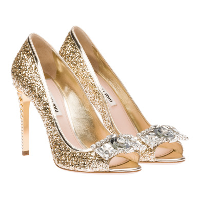 Pour changer un petit peu de la sandale, on aime également cette forme de chaussure. Ce sont des escarpins à bouts ouverts, qu'on appelle en anglais « peep toe ». Cela fait encore plus festif que des escarpins classiques, d'autant que ceux-là attirent les regards ! La chaussure est en effet entièrement recouverte de strass doré. En plus, des bijoux argentés Swarovski sont posés au bout du pied… et les talons hauts sont également recouverts de bijoux ! Cristaux et cerclés dorés viennent en effet encercler le talon. Voilà des chaussures excentriques, idéales si vous voulez casser le côté sobre et classique de votre robe. Chaussures « peep toe », Miu Miu, 895 euros.