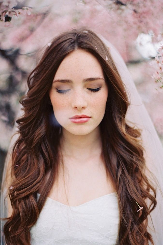 Ici les cheveux sont très longs également, mais coiffés plus simplement. De grosses et fluides ondulations partent sur les côtés, pour dégager le visage et le décolleté. À l'arrière de la tête, la mariée porte son voile bas et seuls quelques pétales de fleurs sont tombés dans ses cheveux. Une vraie coiffure de princesse, idéale si l'on a une belle chevelure épaisse et que l'on veut donner une touche sexy à sa tenue pour contraster avec une robe sobre.