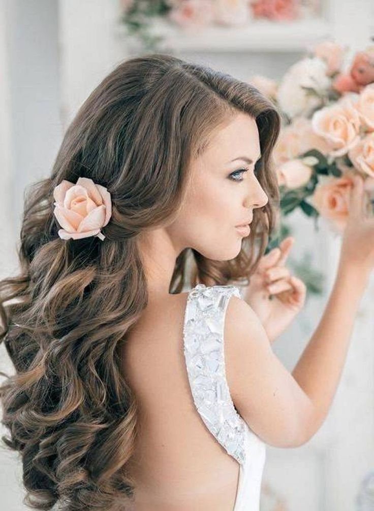 Voilà une autre idée pour coiffer ses longs cheveux ondulés. Côté gauche, une mèche cache un peu le visage par une vague mais côté droit, les mèches sont retenues vers l'arrière de la tête par une belle fleur. Cette rose couleur pêche se marie à merveille avec des cheveux châtains comme ici ! On aime l'idée d'une barrette en fleur pour apporter un petit plus à une coiffure plutôt simple.