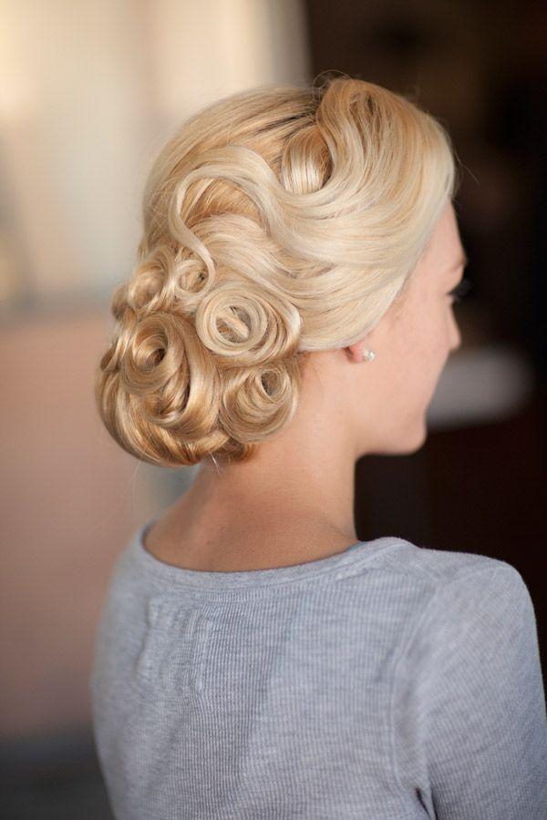 On adore aussi cette coiffure, dans un esprit « fifties ». C'est un chignon bas, « aérien » si l'on peut dire. Pas besoin d'avoir les cheveux trop longs pour cette coupe. Les mèches forment ici de belles boucles sur le bas du chignon, et celles du dessus de la tête font des vagues. C'est une coiffure très travaillée, qui doit nécessiter beaucoup de laque : les cheveux doivent garder leur place ! Le résultat est en tout cas bluffant, très « glamour hollywoodien ».