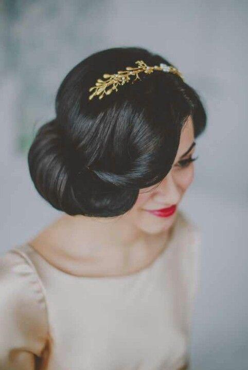Voilà une coupe qui fait également très « tapis rouge » ! La raie des cheveux est placée à gauche et le chignon est noué à droite. Il est volumineux, fluide. Le bas des mèches est enroulé sur lui-même au niveau des pommettes. Une mèche de cheveu revient joliment sur le visage. Très sexy comme résultat ! Et petite touche d'originalité en plus : ce serre-tête doré, qui se marie à merveille avec des cheveux noirs comme ici. Cet accessoire ressemble à une branche de laurier, et ajoute un côté festif à la coiffure, car après tout le mariage est une fête ! Ce chignon nécessite une certaine longueur de cheveux, pour avoir un maximum de volume sur le côté roulé.