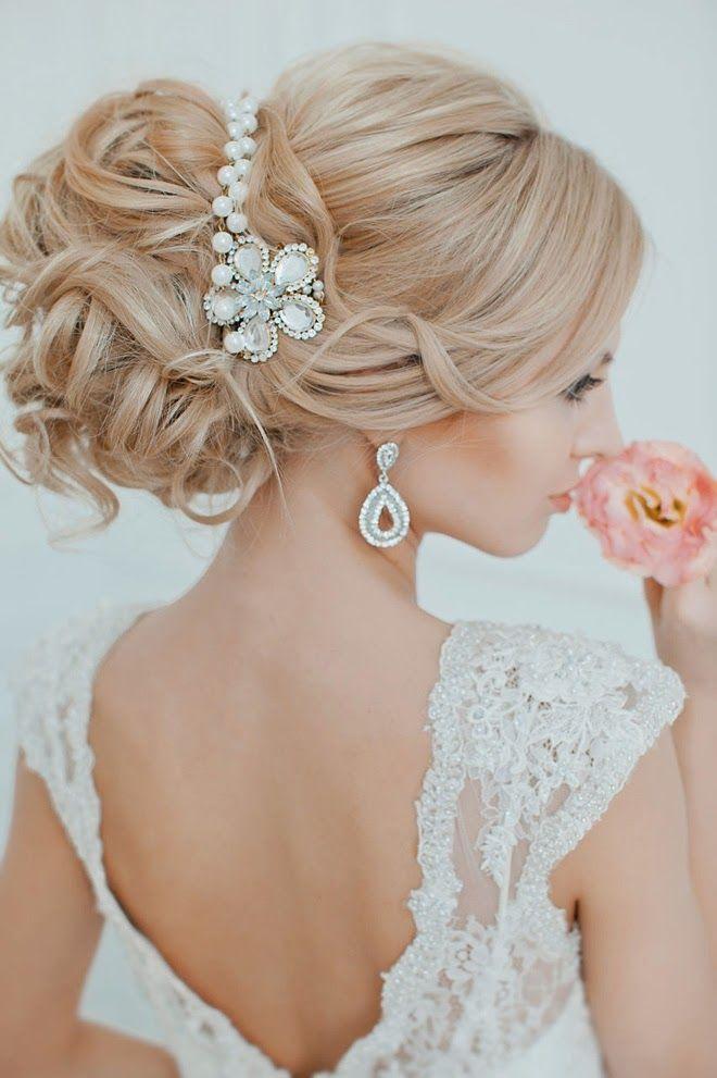 Plus fantasque et imposante, on aime beaucoup aussi cette coiffure ! Des cheveux longs à très longs sont nécessaires pour former le volume de ce gros chignon. Il est fluide, un peu « foufou ». Quelques mèches de cheveux reviennent délicatement sur le devant du visage. À l'arrière de la tête, le chignon est noué assez haut, avec des boucles, des mèches rebelles… Originalité de la coiffure, ce headband fait de bijoux blanc et argent, très bien assorti aux boucles d'oreilles de la mariée. Cette coupe permet de montrer son dos dans cette robe en dentelle décolletée.