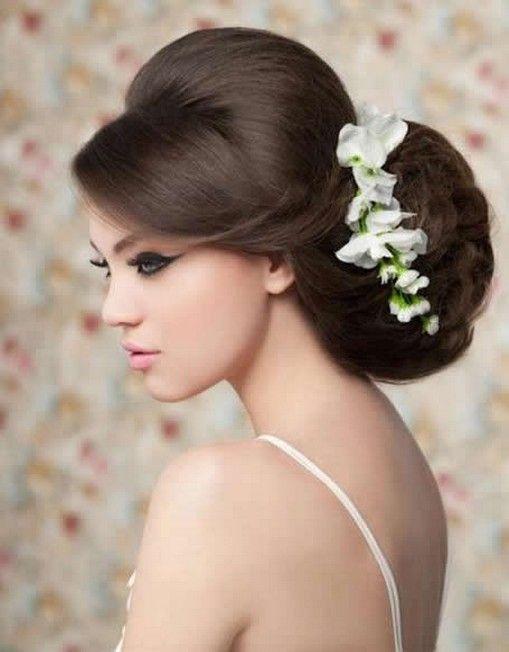 Le maître-mot de ce chignon est : du volume ! Si vous voulez dompter votre longue et épaisse chevelure, cette coupe est faite pour vous. Une grosse mèche vient cacher un petit peu le devant du visage, par une vague glamour. Les cheveux prennent ensuite beaucoup de hauteur et sont noués en un très gros chignon, très fluide, à l'arrière de la tête. Une bonne dose de laque a dû être nécessaire ! Et pour compléter cette coiffure digne d'une actrice de cinéma, des fleurs blanches viennent se marier avec les cheveux châtains. Une coupe idéale si votre robe est un peu trop classique.