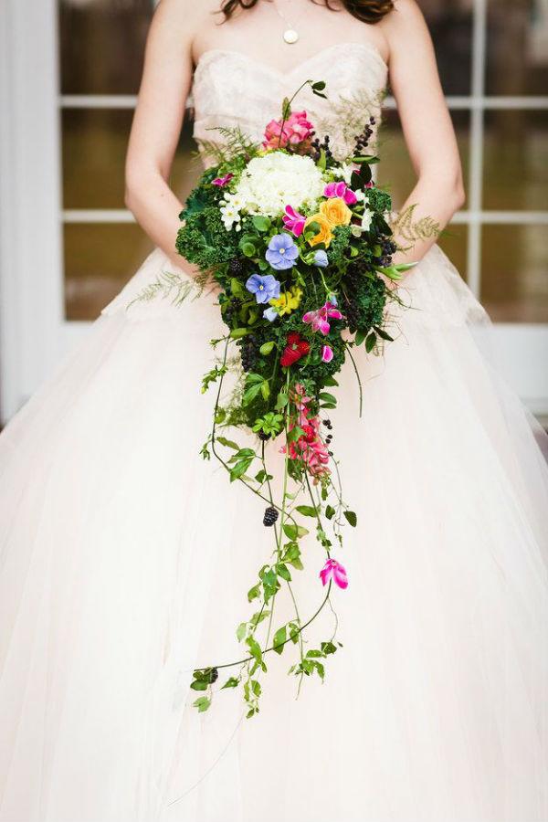 Voilà un autre bouquet bohème, assez fouillis, qui donnera une touche rock à une robe de mariée un peu trop sage. Beaucoup de verdure constitue ce bouquet, et l'on dirait que les petites fleurs colorées ont été piquées dedans. Seules quelques feuilles tombent du bouquet, comme si elles voulaient s'en échapper ! Blanc, mauve, rose, jaune… on trouve de toutes les couleurs dans cette composition, y compris des fruits ! Oui, n'avez-vous pas vu les mûres au milieu des feuilles ? Génial, comme idée !