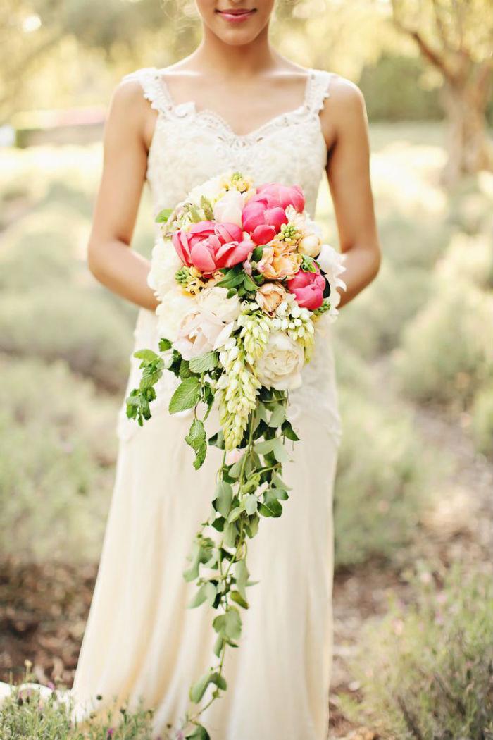 Plus majestueux, la verdure de ce gros bouquet descend jusqu'aux pieds de la mariée, carrément ! Le blanc, le rose, le beige et le jaune se mêlent au vert pour un rendu très coloré, gai et généreux. On imagine bien cette composition assortie à une robe en dentelle.