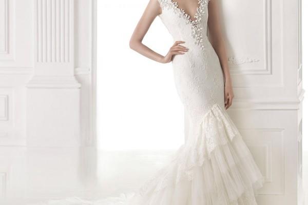 Cette robe Pronovias de la collection 2015, est idéale pour les grandes mariées. Son fourreau de dentelle en bas de la robe, permet de casser de manière élégante le possible effet ''grande perche''. Son décolleté sexy est idéal pour les petites poitrines.