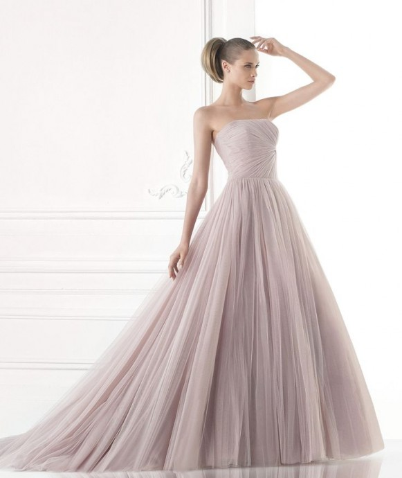 La teinte rose de la robe Malaike de chez Pronovias permet à toutes celles qui ont la peau clair d'enfin porter du rose. De plus, elle également parfaite pour les cheveux et les peaux plus foncés.