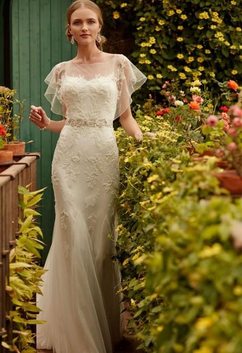 BHLDN joue la simplicité avec un accessoire de tulle fin à la forme arrondie qui viendra délicatement recouvrir vos épaules. On aime l'effet manches courtes qui habille la robe.