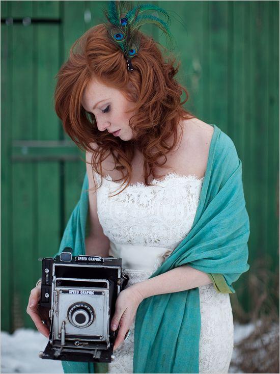 On commence cette sélection de 10 coiffures par des plumes de paon, l'oiseau que l'on voit le plus s'immiscer dans les chevelures. Cette mariée a laissé ses beaux cheveux roux et bouclés lâches. Elle porte une grande barrette qui lui retient une mèche sur le côté gauche. 3 grandes plumes de paon resserrées en bouquet sont attachées à la pince. Magnifiques, ces teintes bleu-vert, n'est-ce pas ? En plus, le châle turquoise portée sur les épaules de la mariée, par-dessus sa robe bustier, se marie à merveille avec l'accessoire de cheveux.