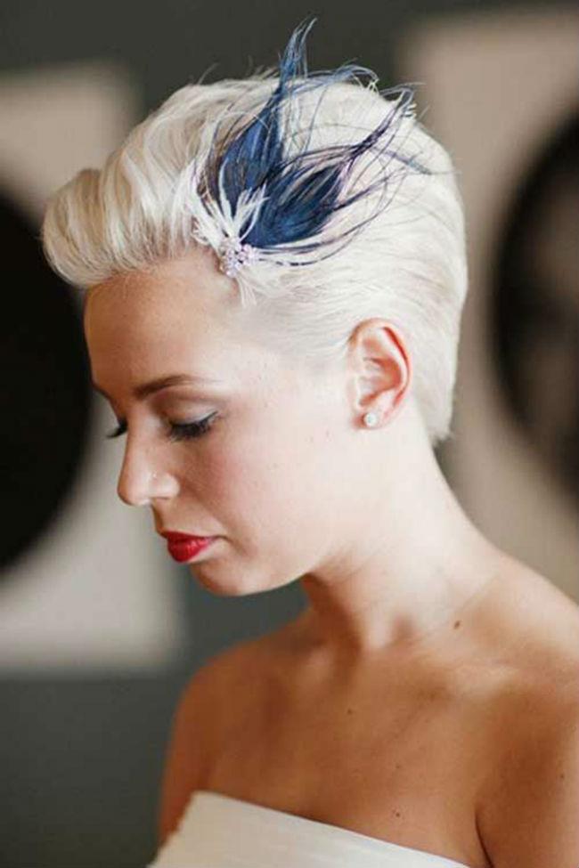 Les cheveux courts ont aussi droit aux plumes ! Les cheveux blancs de la mariée sont assortis à sa robe bustier. Sa coupe en brosse est accessoirisée par ces belles plumes blanches et bleues. Les deux couleurs se mêlent bien et la teinte bleu nuit apporte du peps au look. Un petit bijou argenté complète cette barrette et s'associe très bien aux boucles d'oreilles discrètes. Côté maquillage, un beau rouge à lèvres rouge sang vient dynamiser l'ensemble.