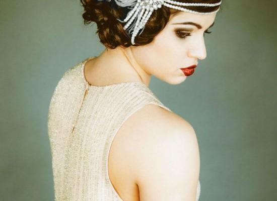 On flashe pour ce look rétro années 20 ! Les cheveux bouclés sont attachés en chignon très fluide : les cheveux ne sont pas du tout tirés, une mèche revient sur le front. La chevelure est agrémentée d'un head band majestueux constitué de deux rangs de perles blanches, d'un grand bijou composé de ces mêmes perles en forme de rosace et de rubans, et enfin d'une gigantesque plume blanche. Avec un tel accessoire, vous ne passerez pas inaperçue ! Pour compléter ce look « Gatsby le Magnifique », rien de tel qu'un maquillage prononcé et une robe droite écru à strass comme ici.