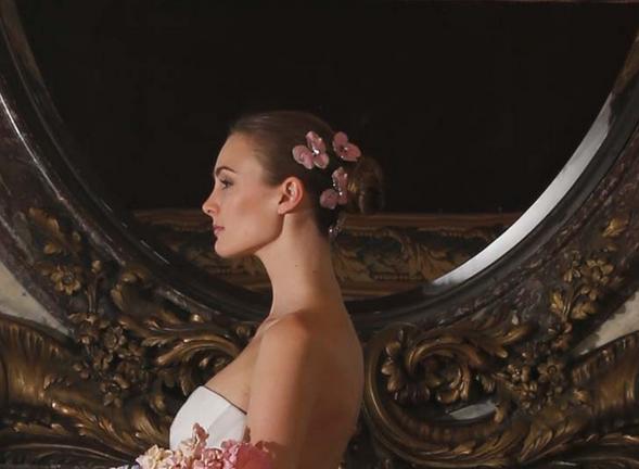 Chignon tiré agrémenté de fleur rose en raccord avec le bouquet de la mariée Pour Romona Keveza. On aime cette petite touche de couleur girly qui anime l'ensemble.