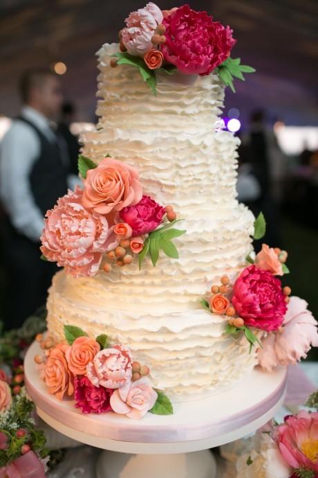 Quatre étages de gourmandises pour ce ruffle cake. Les fleurs viennent parfaire ce gâteau.