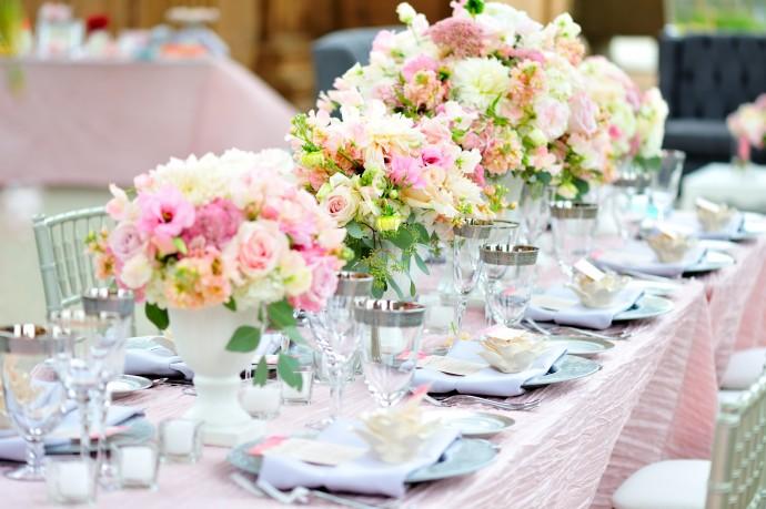 Une nappe rose poudré, des assiettes bleu givré et des fleurs roses pâles pour une décoration de thème romantique.