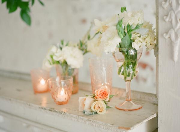 Des bougeoirs ton pêche et des verres orangés en guise de vases pour une décoration pastel et pêchue.