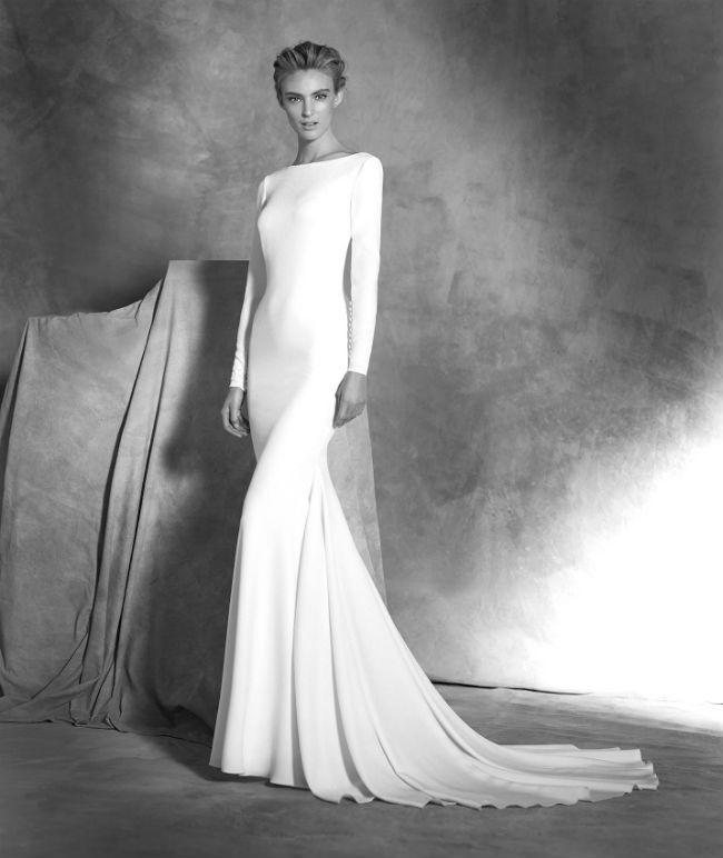 Cette robe a aussi une coupe sirène : elle est donc moulante jusqu'aux genoux avec ensuite une base évasée et plissée. Si vous êtes à l'aise avec votre corps le résultat pourra être très sexy. D'autres mariées préféreront une robe fluide voire ample. Celle-ci est en crêpe, à col bateau droit et manches longues. On aime les boutons aux poignets : un détail original et plein de charme. Un décolleté plongeant en V dans le dos rend la robe encore plus sensuelle. La bonne idée : avoir les cheveux attachés pour qu'on puisse bien l'admirer, et porter un collier coloré pour donner une touche d'excentricité à l'avant. Robe Ivania, Pronovias, à partir de 2 200 euros.
