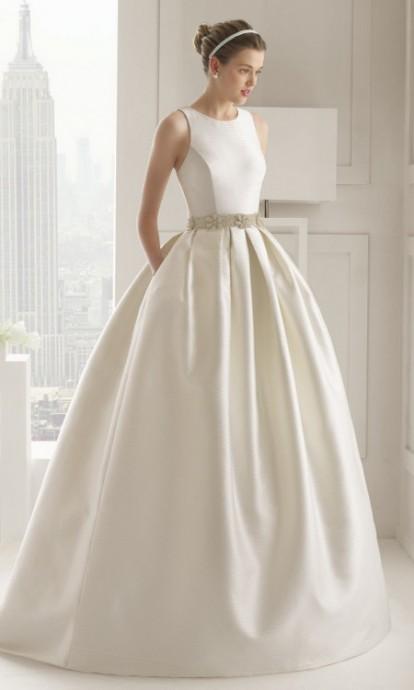 Une vraie robe de poupée, un buste simple et élégant séparé du jupon par une petite ceinture fleurie. Les poches sont complètement fondues dans le volume de la robe. Modèle Sensual de chez Rosa Clara.