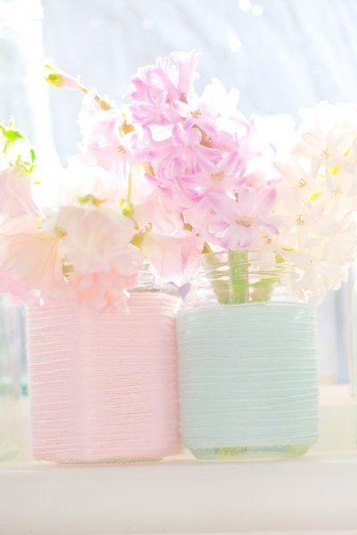 Des bocaux recouverts de fils rose et vert pastel pour accueillir vos fleurs de mariage.
