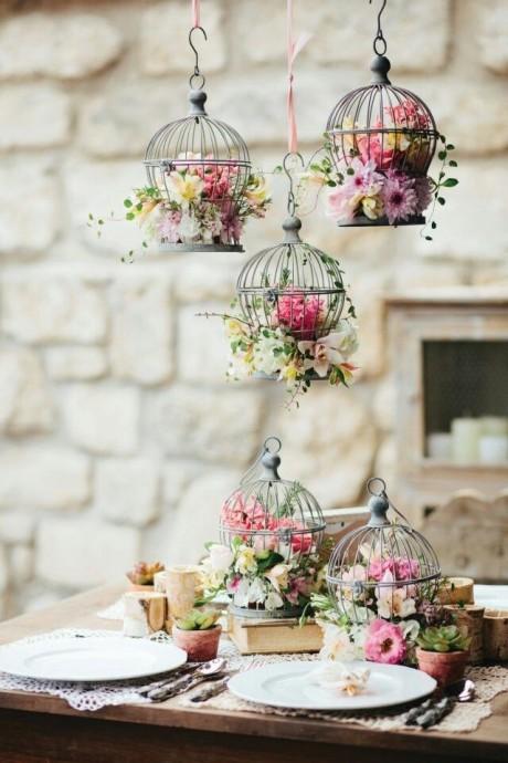 Les cages à oiseaux peuvent avoir de nombreuses utilités dans la décoration d'un mariage. Ici, on les utilise pour embellir encore des fleurs et les installer en hauteur.