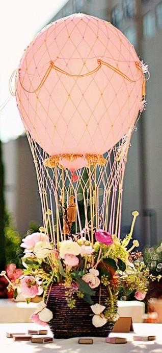 Un joli centre de table mongolfière agrémenté de fleurs sauvages; Idéal si  les mariés sont de vrais globe-trotters.
