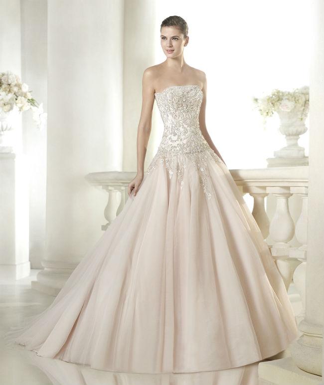Ici c'est tout le bustier qui est incrusté de petits bijoux, à strass argentés, dans un motif floral. Ils descendent jusqu'au haut du jupon. Celui-ci est plissé, d'une teinte rose poudré très délicate. Cela change des traditionnelles robes blanches, tout en gardant cette douceur propre aux tenues de mariage. On aime également le décolleté dans le dos, un petit plus profond qu'à l'avant, en forme de V. Le haut de la robe étant tout incrusté de pierreries, mieux vaut éviter de porter des bijoux trop imposants. Robe « Cherry Style, Glamour », St Patrick Barcelona, prix non communiqué.