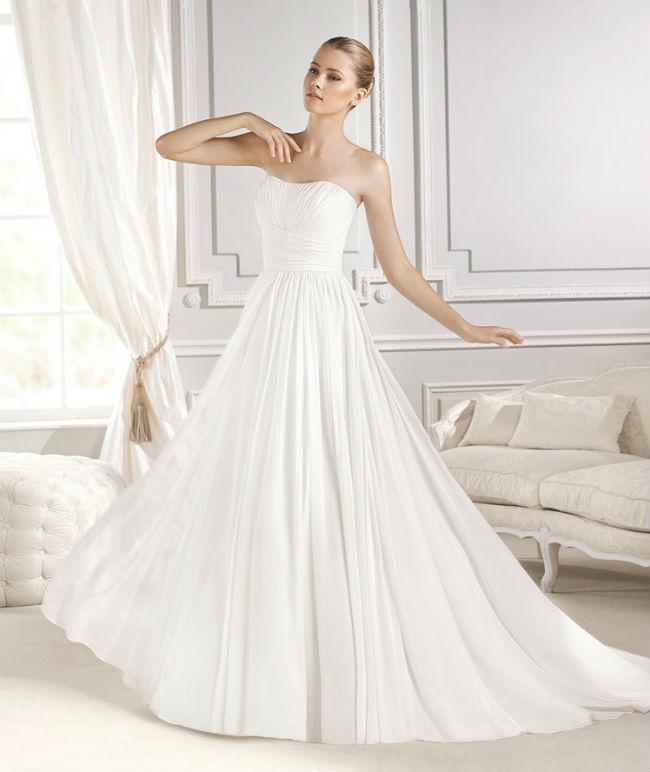 La simplicité, c'est parfois ce qu'il y a de mieux ! Cette robe n'a pas de dentelle, de bijoux incrustés ou d'accessoire particulier, mais elle est splendide. Blanche, elle est toute drapée. Cette multitude de plis fait tout le charme de cette robe bustier. Les pans de tissu sont comme croisés au niveau de la taille pour un rendu des plus élégants. La robe étant sobre, vous pouvez vous permettre de porter un maquillage prononcé, des bijoux étincelants ou bien un long voile avec de belles broderies. Robe « Eithel Style, Fashion », La Sposa Barcelona, prix non communiqué.