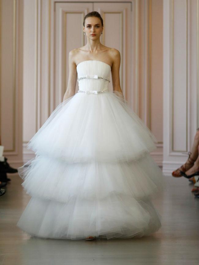 Cette robe-ci est plus extravagante, tout en gardant les codes de la robe de mariée. Blanche, elle est à bustier légèrement drapé. Celui-ci est entouré de 2 ceintures à bijoux brillants et nœuds sur le devant. De beaux accessoires qui donnent toute son originalité à la robe. Son excentricité vient de son triple jupon très très volumineux, comme les tutus de danseuses étoiles… en trois fois. Dans votre salle de réception de mariage, on ne verra que vous, c'est sûr ! Avec cette robe, on peut se permettre de porter un beau rouge à lèvres pour avoir une touche de couleur, mais on évite les gros bijoux pour ne pas faire accumulation. Robe Oscar de la Renta, prix non communiqué.