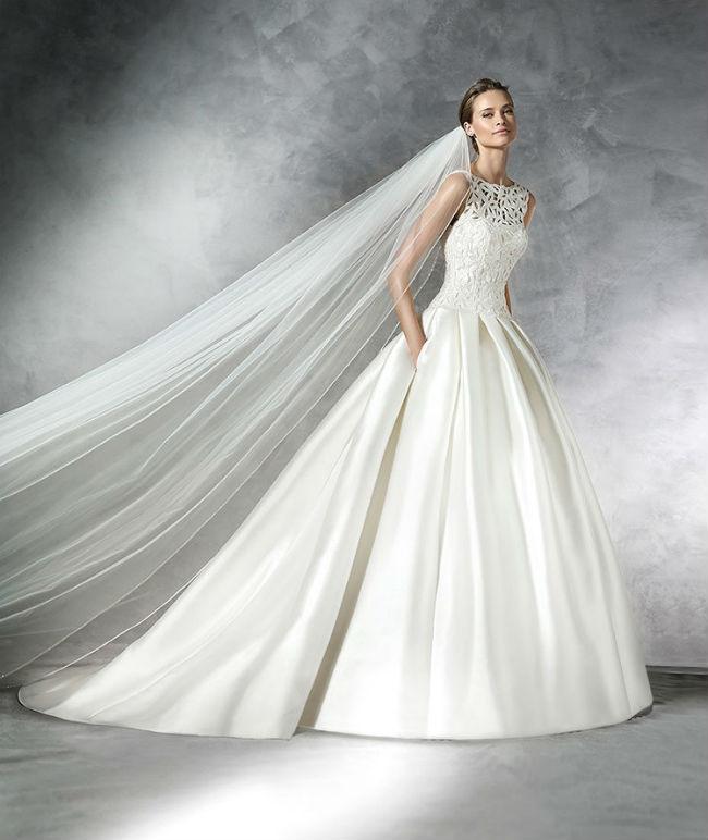 Que dites-vous de cette robe au buste à col bateau, recouvert de passementeries ? Ces formes entrelacées sont splendides ! L'arrière est très décolleté : sexy mais pas vulgaire. Enfin, le jupon en mikado de soie est plissé, avec une belle tenue. Si l'envie vous en dit, vous pouvez porter cette robe avec un long voile plissé, comme le mannequin, et vous vous assurerez un look de reine ! Les princesses de Monaco n'ont qu'à bien se tenir ! Robe « Pranette », Pronovias, à partir de 2 290 euros.