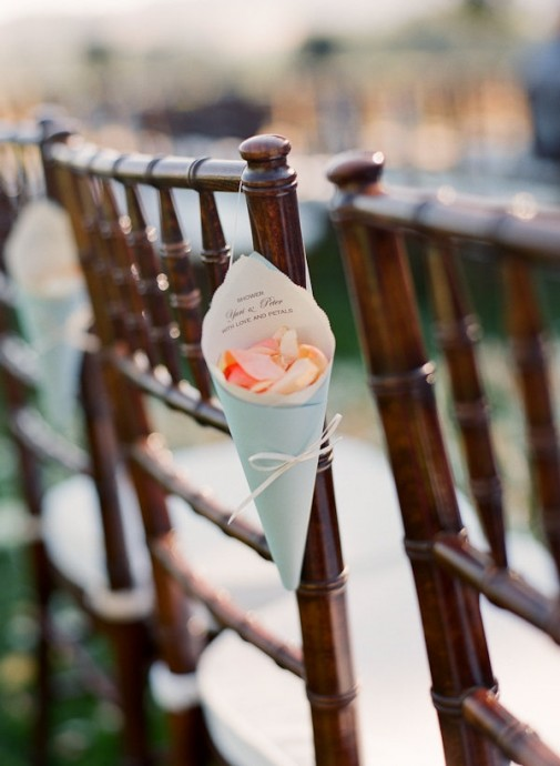 Encore une bonne idée pour couvrir les pas de la mariée s'avançant vers l'autel de pétales. Accrochez au dossier de plusieurs chaises près de l'allée de jolis cornets de la couleur que vous désirez et remplis de pétales. Ainsi les convives qui se trouveront à proximité pourront participer à la cérémonie et vous lancer quelques fleurs. On aime cette idée et on économise ainsi une petite lanceuse de fleurs pour la cérémonie.