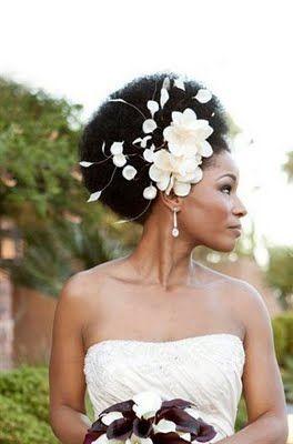 Super la coupe afro pour un look seventies ! Mais pas n'importe lequel, on ajoute la touche chic avec une jolie coiffe sur le côté de la tête et on ne lésine pas sur le volume. Pourquoi ne pas piquer quelques plumes légères qui mettront en valeur le volume de vos cheveux et l'arrondi de votre coupe ? Parfait pour un mariage chic et choc !