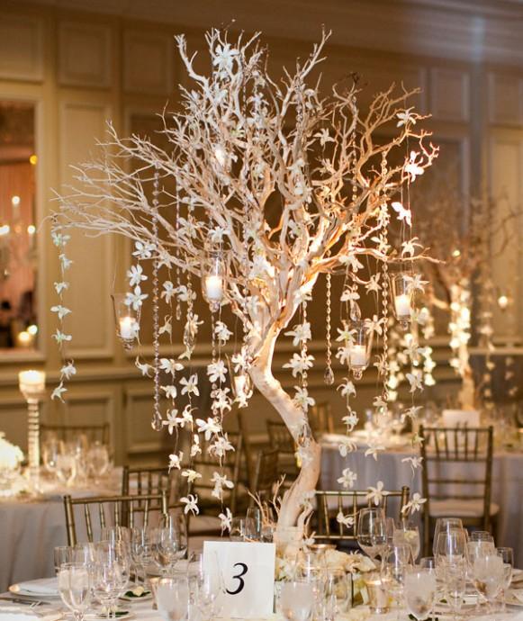 On adore ce centre de table en forme d'arbre dénudé, habillé de petites guirlandes de fleurs et de photophores. Le tout donne un effet très naturel et romantique. Le bois apporte du cachet à votre décoration, nous on craque !
