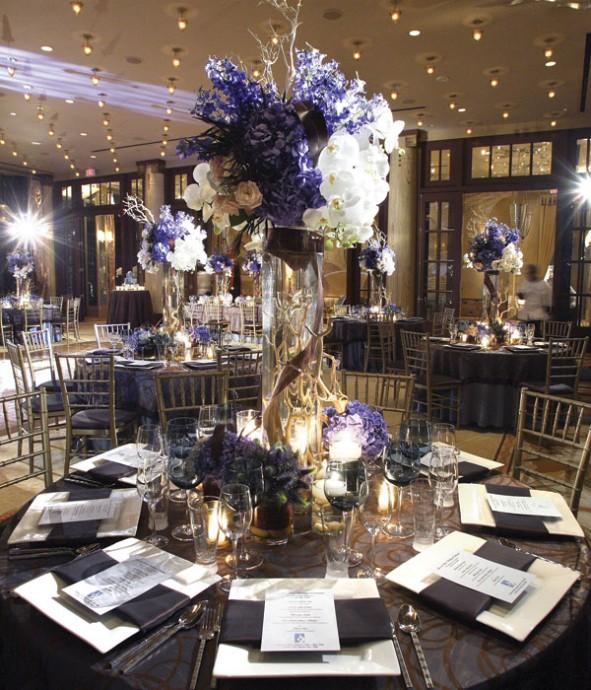Très chic ce centre de table esprit citadin et hôtel chic. Différentes variétés de fleurs sont mélangées dans cette composition blanche et mauve et dans le vase, par transparence, on peut voir des branchages qui remonte jusqu'au sommet de la composition. Magnifique !