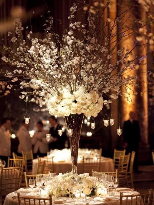 Encore une fois voici un centre de table tout en hauteur en roses blanches avec des branchages qui s'échappent vers le haut. De plus les petits photophores créent une ambiance tamisée très cosy.