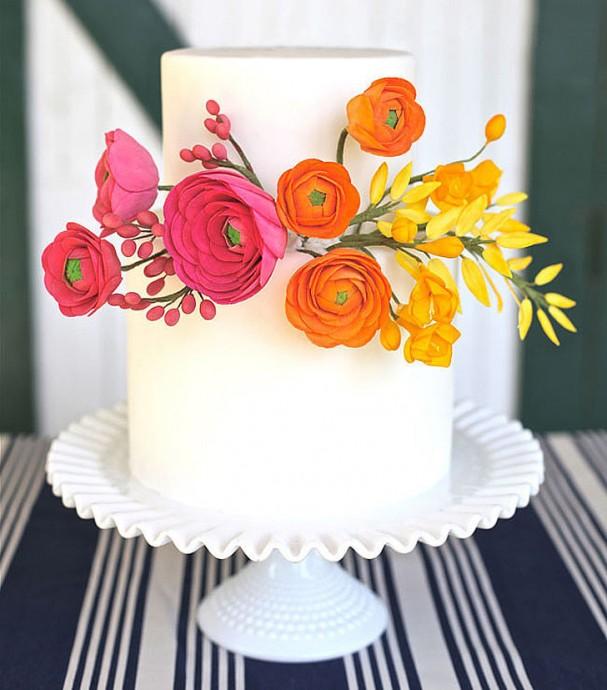 Pour un mariage haut en couleurs ou bien estival, ce wedding cake peut vous faire craquer. Simple, blanc, mais décoré de fleurs multicolores, nous on trouve le rendu magnifique.
