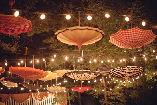 """Un petit côté """"Les Parapluies de Cherbourg"""" cette décoration suspendue, non ? Mais on trouve l'idée super originale et le rendu magnifique. Choisissez donc avec soin quelques ombrelles et parapluies vintages et dépareillés et pendez-les par la poignée au dessus de vos invités. Le tout au milieu de guirlandes lumineuses pour les mettre en valeur. Cette décoration ira parfaitement dans un mariage bohème ou vintage. Alors qu'attendez-vous pour piquer l'idée ?"""