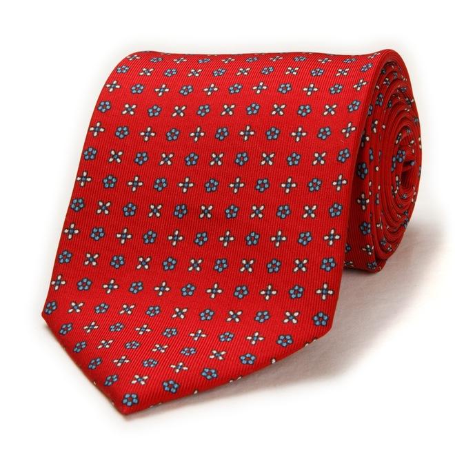 Cette cravate rouge aux fleurs blanches et bleues Corso Mille est très sympa avec un costume qu'il soit noir, bleu marine ou gris.